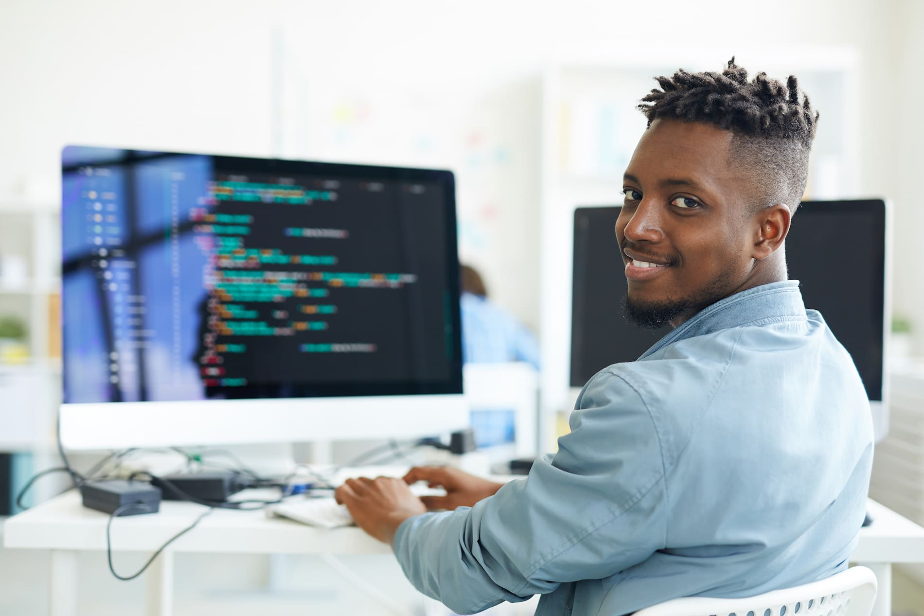 Happy guy looking at camera while sitting by workplace and working with software
